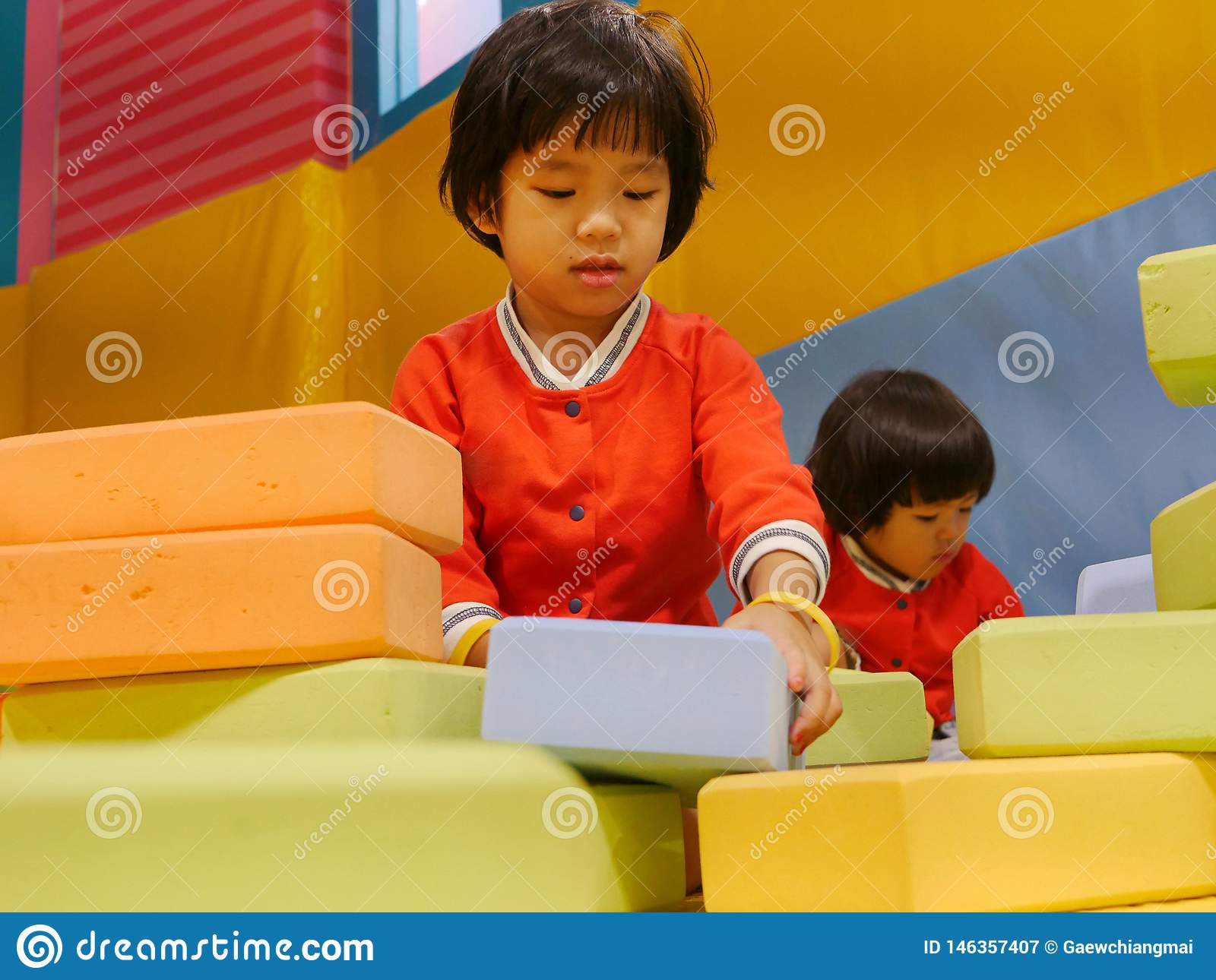 Two Little Asian Baby Girls Sisters Stacking Up Foam Building Bricks Blocks Together At An Indoor Playground Stock Image Image Of Hand Helps 146357407