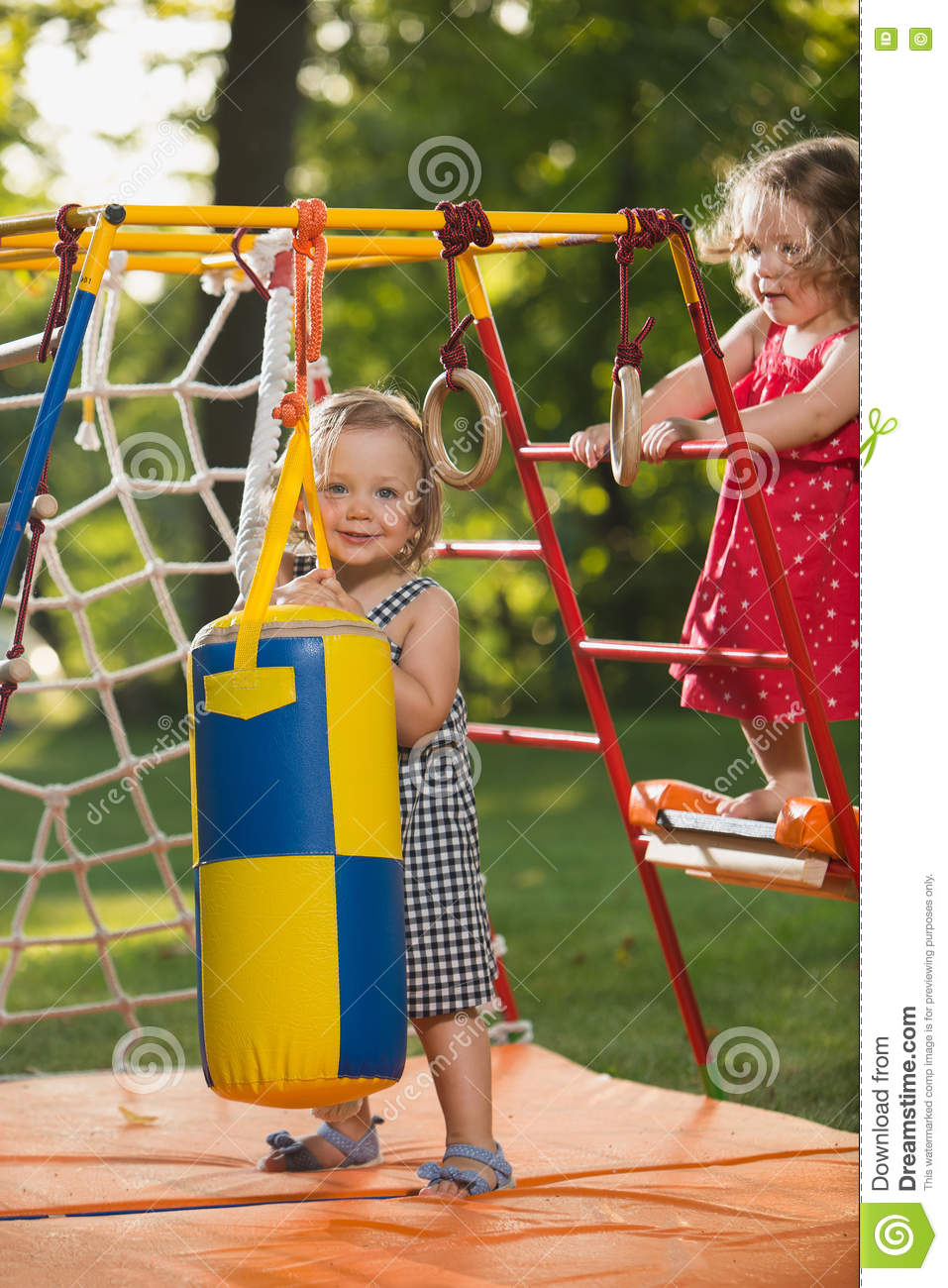 The two little baby girls playing at outdoor playground