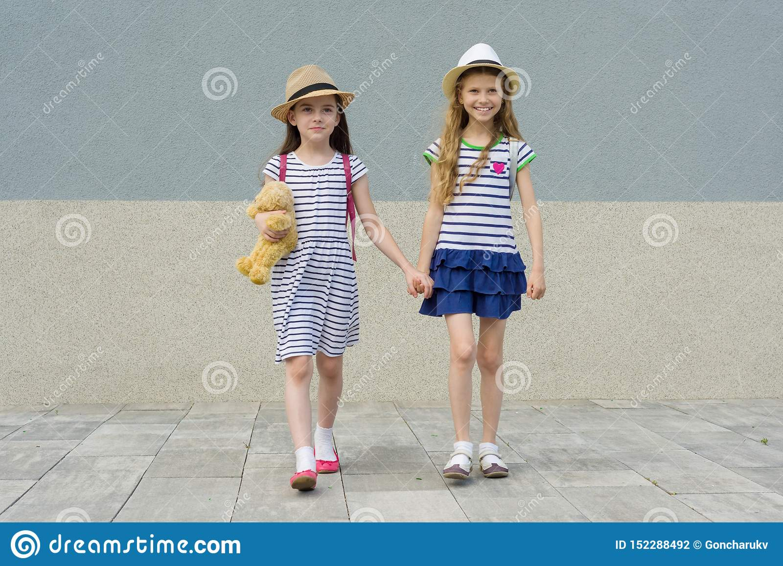 Two little beautiful girlfriends holding hands, girls walking in striped dresses, hats with backpack