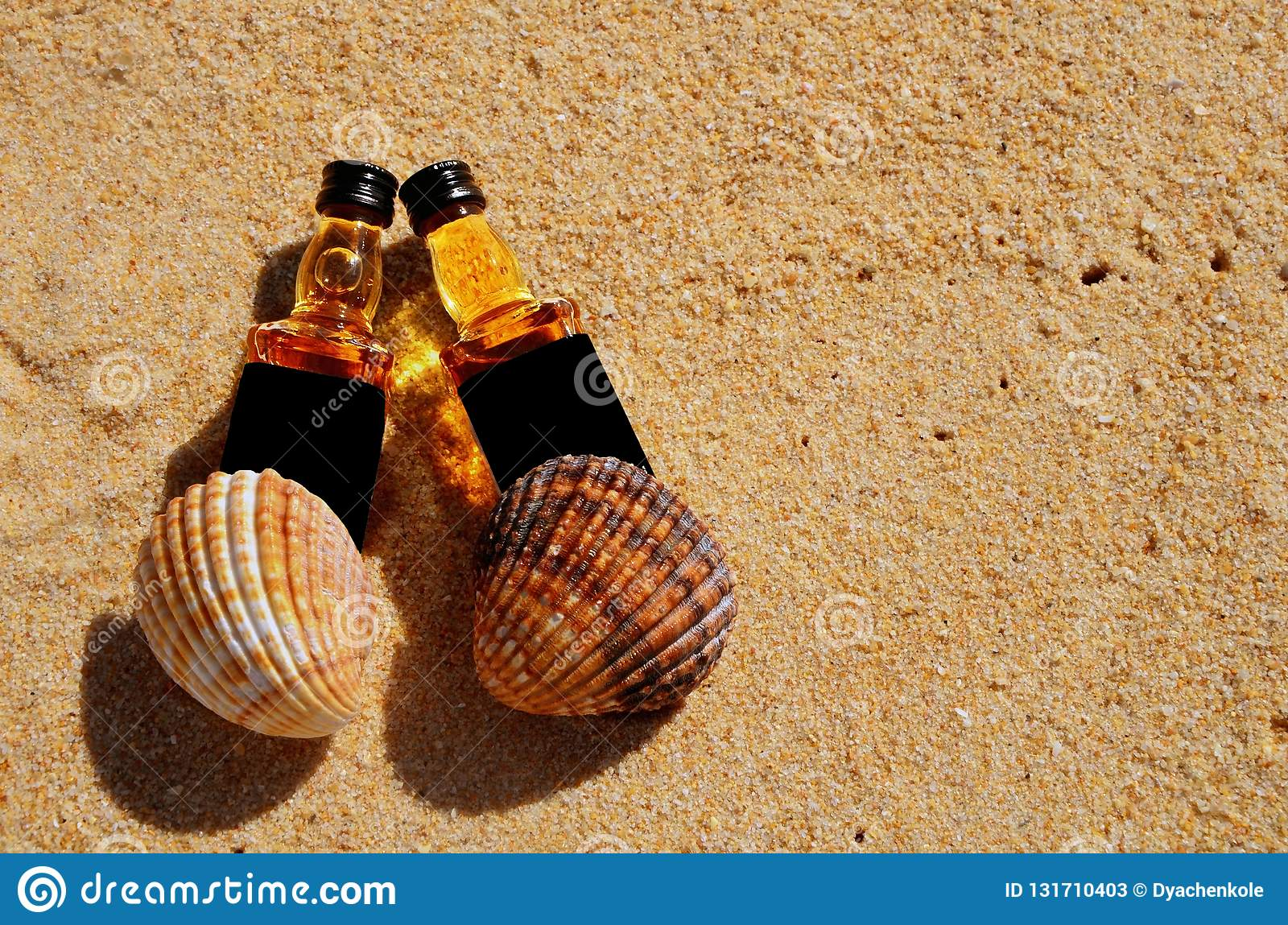 Two little bottles whiskey lie on the sand. Alcohol top view from above