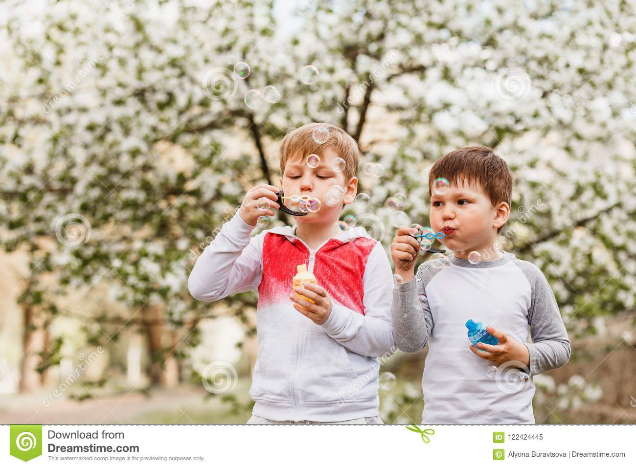Two boys inflate soap bubbles in the summer outdoors