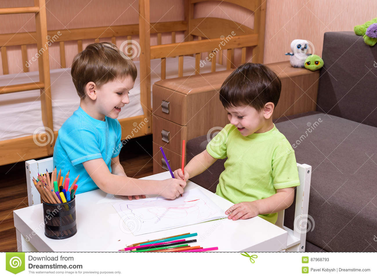 Two little caucasian friends playing with lots of colorful plastic blocks indoor. Active kid boys, siblings having fun building an