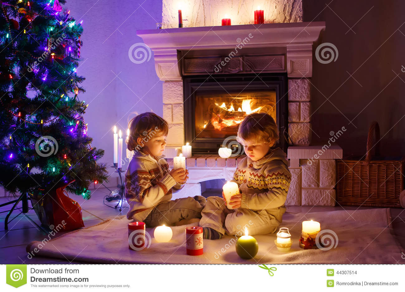 Two little children sitting by a fireplace at home on for At home christmas