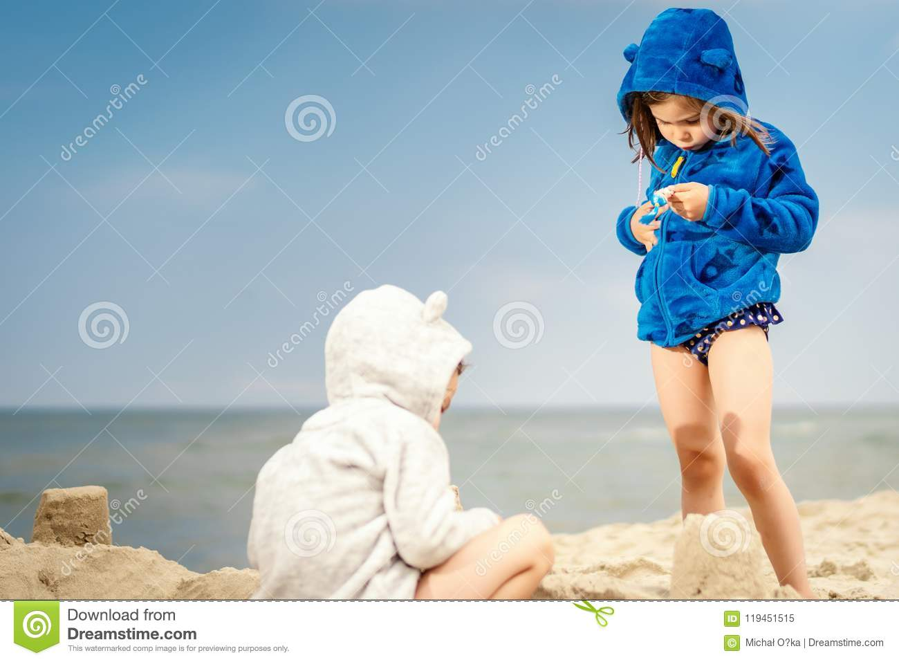 Two Little Cute Girls Playing On The Sand At The Beach Stock Image