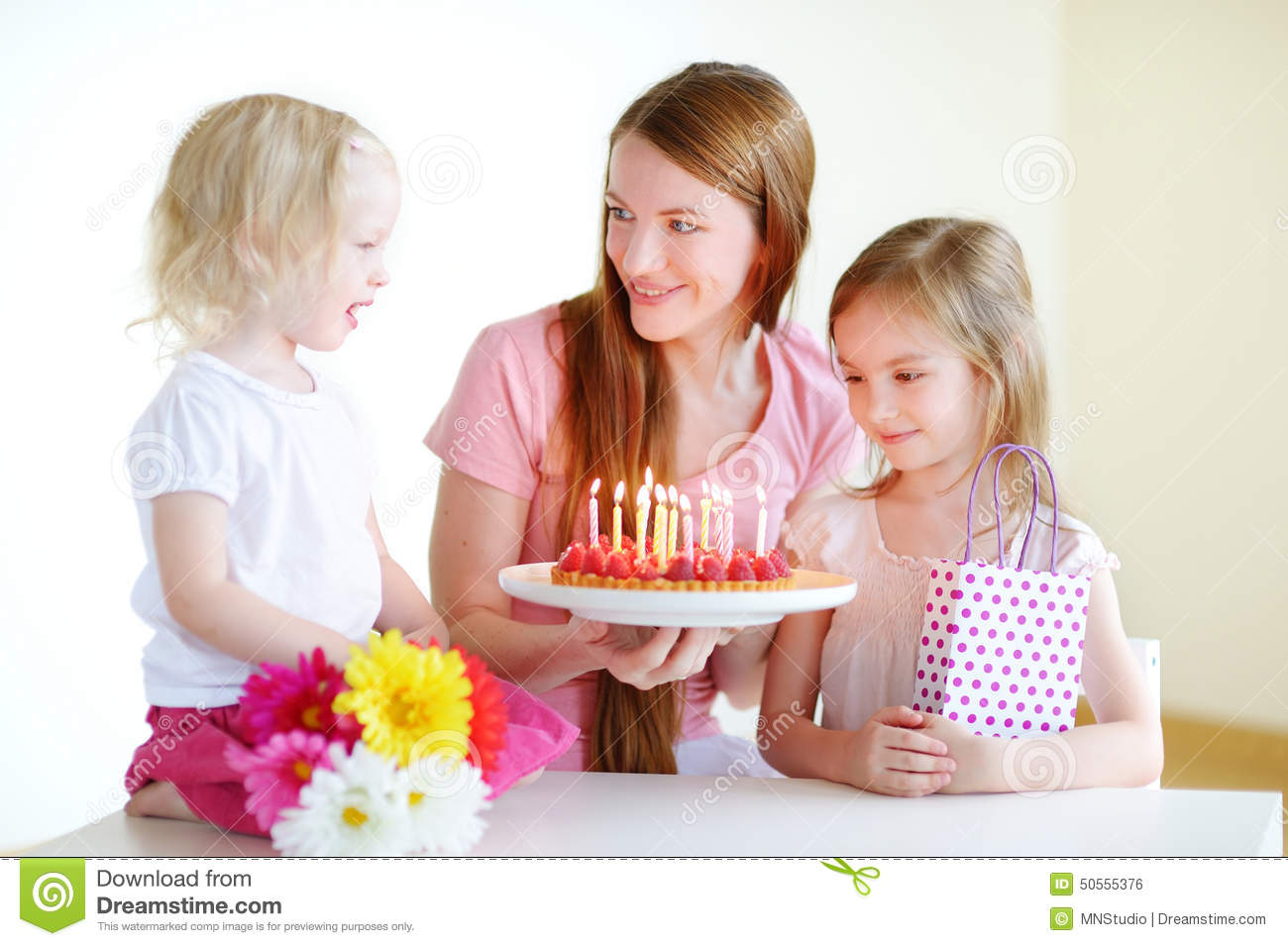 Two little daughters and mom with birthday cake