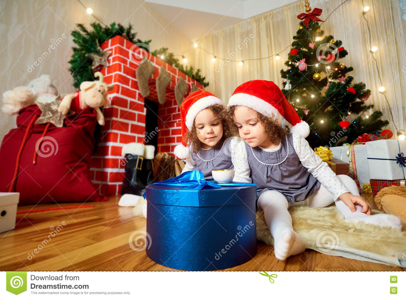 Two little girls in caps of Santa Claus sitting on the floor with gifts in  the room with the Christmas tree. 0969a44d5803