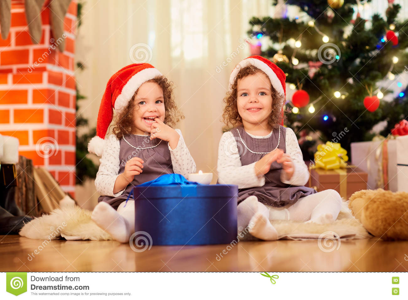 Two little girls in caps of Santa Claus sitting on the floor wit