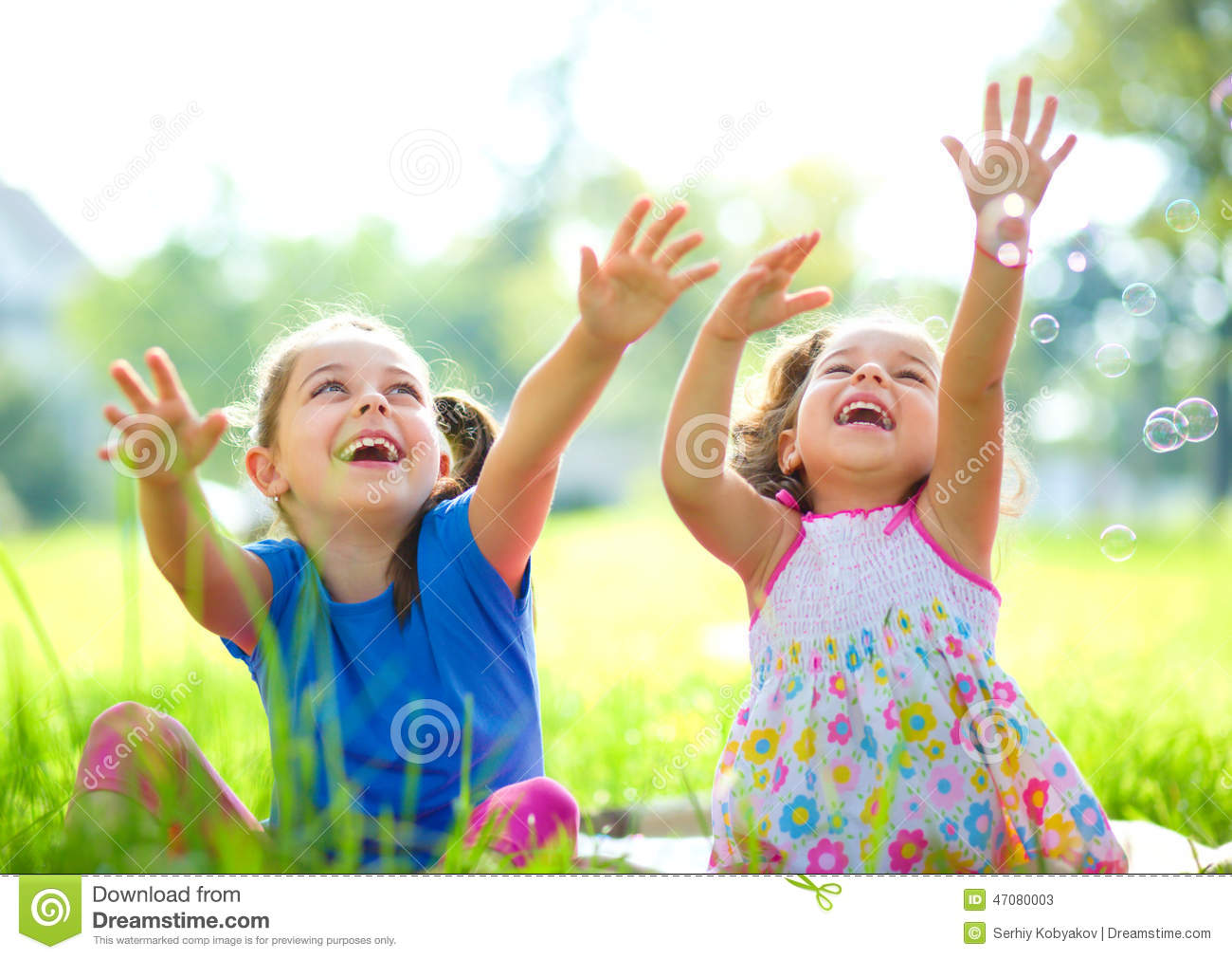 Two little girls are catching soap bubbles