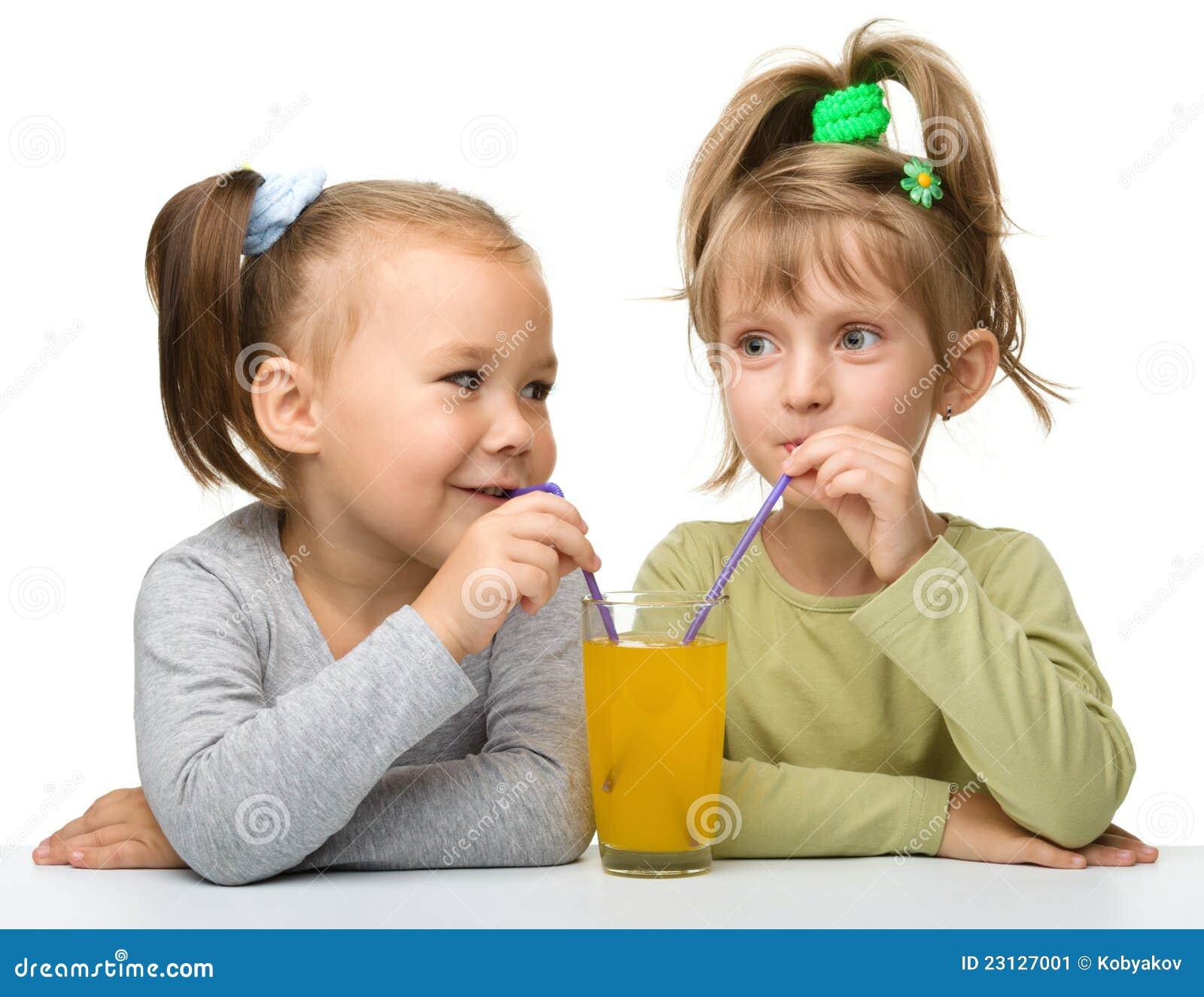 Two little girls are drinking orange juice