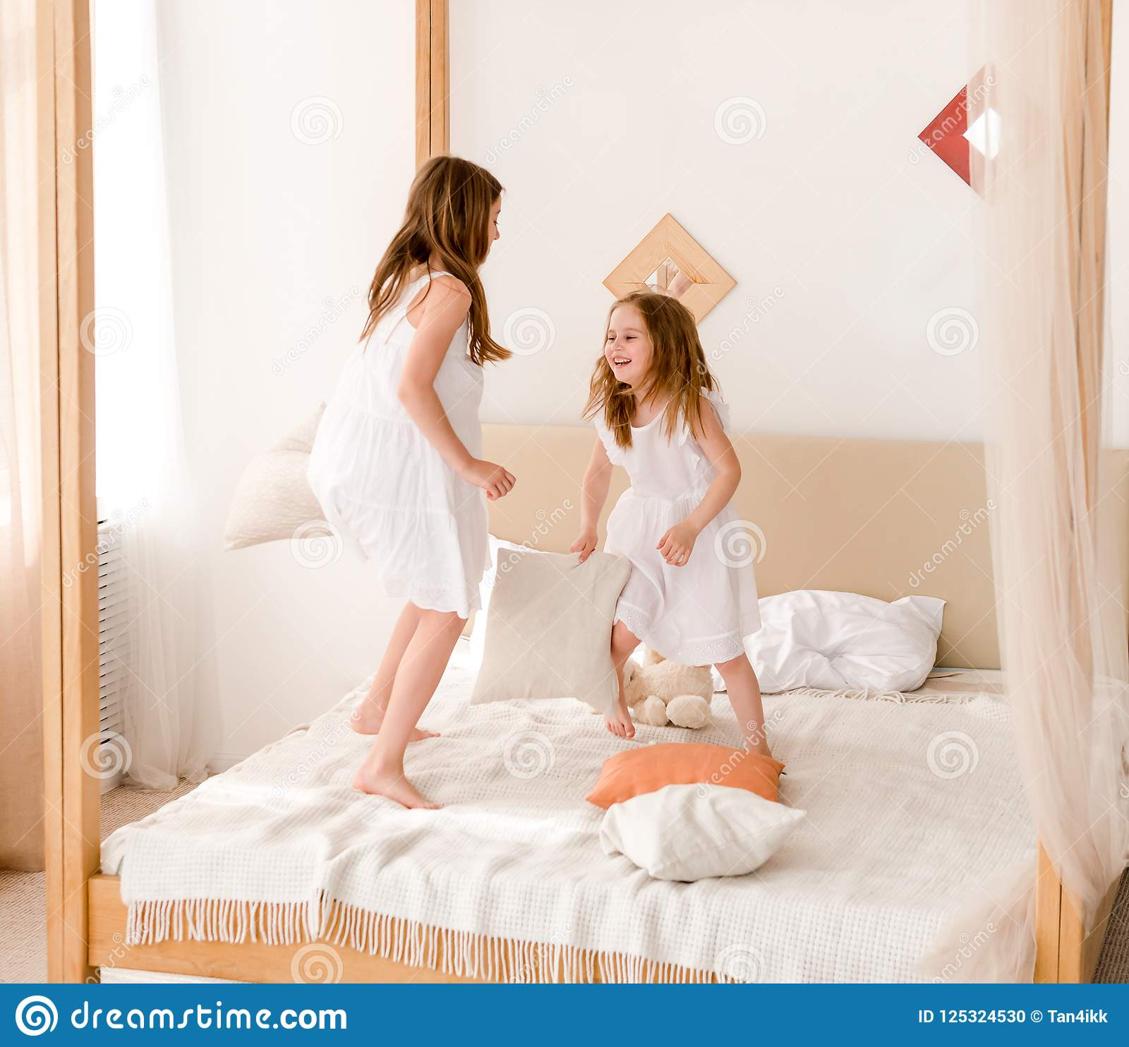Two little girls fighting with pillows on the bed