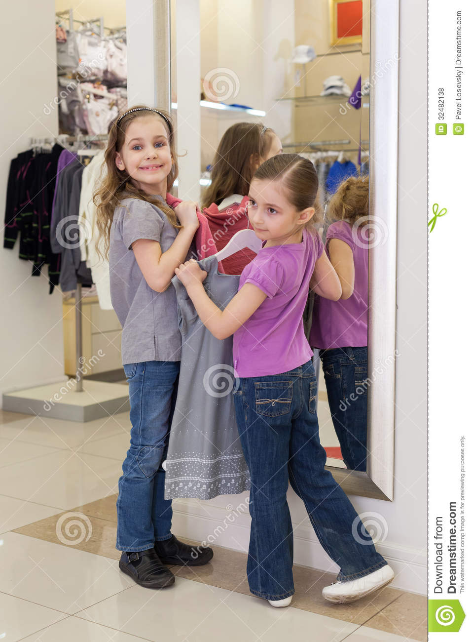 little girls near a mirror try on clothes in a store childrens clothes