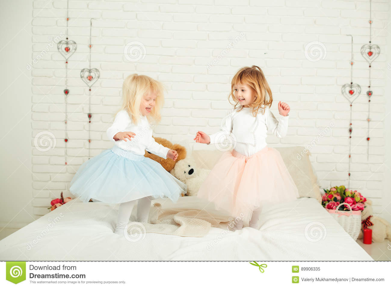 Two little girls in nice dresses in fun jumping on a bed.