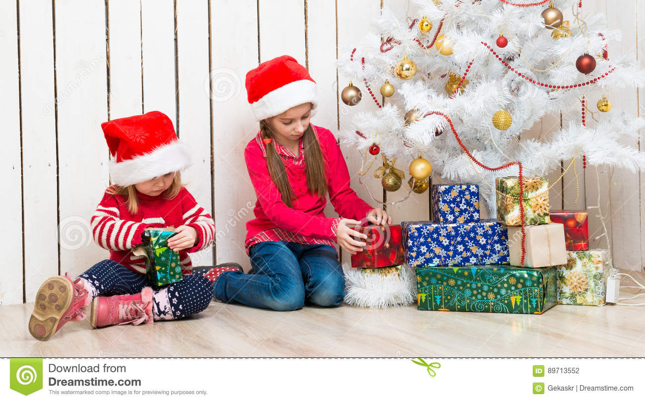 Christmas Presents For Girls.Two Little Girls Open Christmas Presents Sitting On The