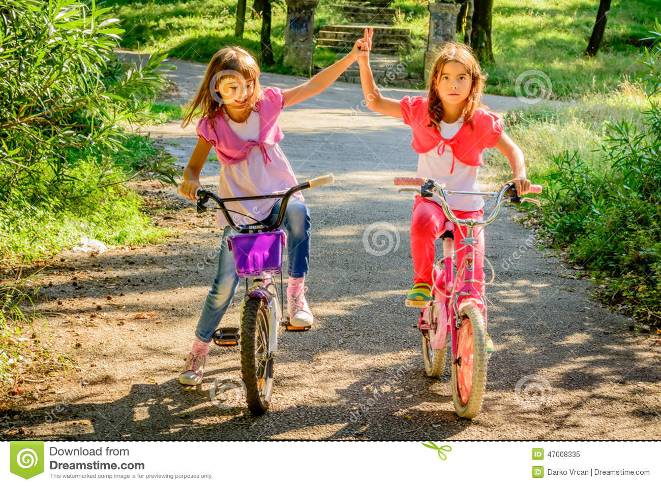 ... Photo: Two little girls riding bikes and playing with each other