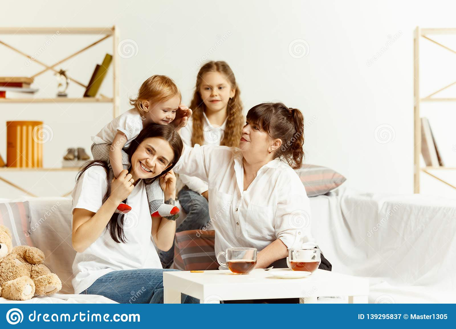 Little girls, attractive young mother and charming grandmother are sitting at home