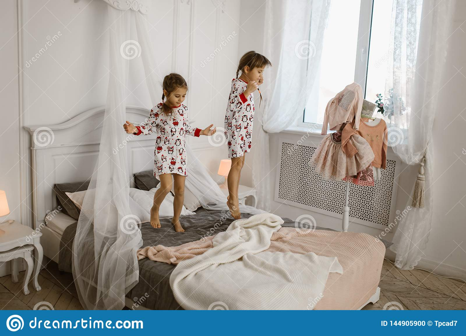 Two Little Girls In Their Pajamas Are Having Fun Jumping On A Bed In A Sunlit Cozy Bedroom Stock Photo Image Of Cute Celebration 144905900