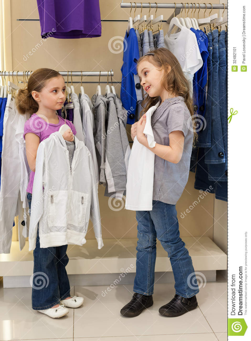 Two little girls try on clothes in a store childrens clothes