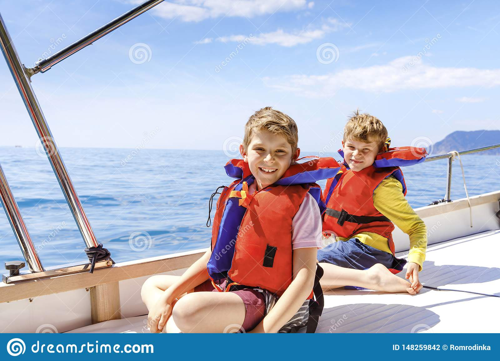 Two little kid boys, best friends enjoying sailing boat trip. Family vacations on ocean or sea on sunny day. Children