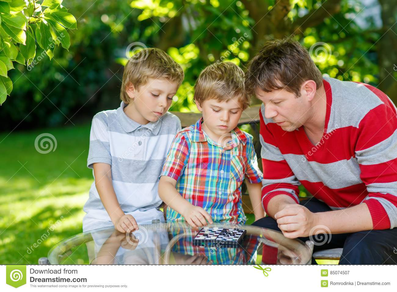 Two little kid boys and father playing together checkers game