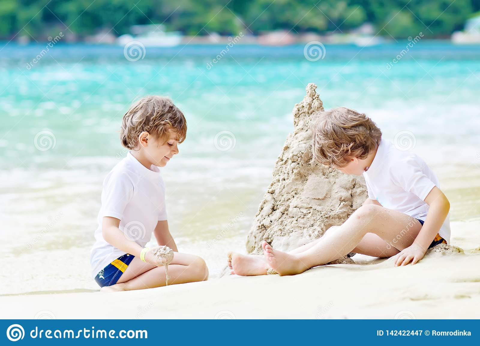 Two little kids boys having fun with building a sand castle on tropical beach of Seychelles. children playing together