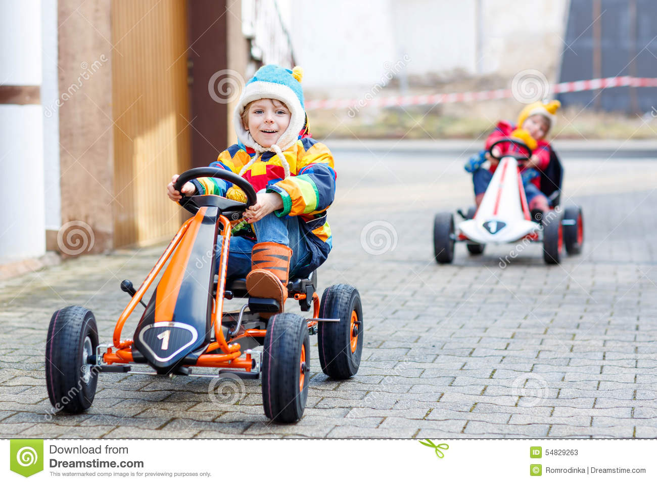 two little kids boys having fun with toy race cars