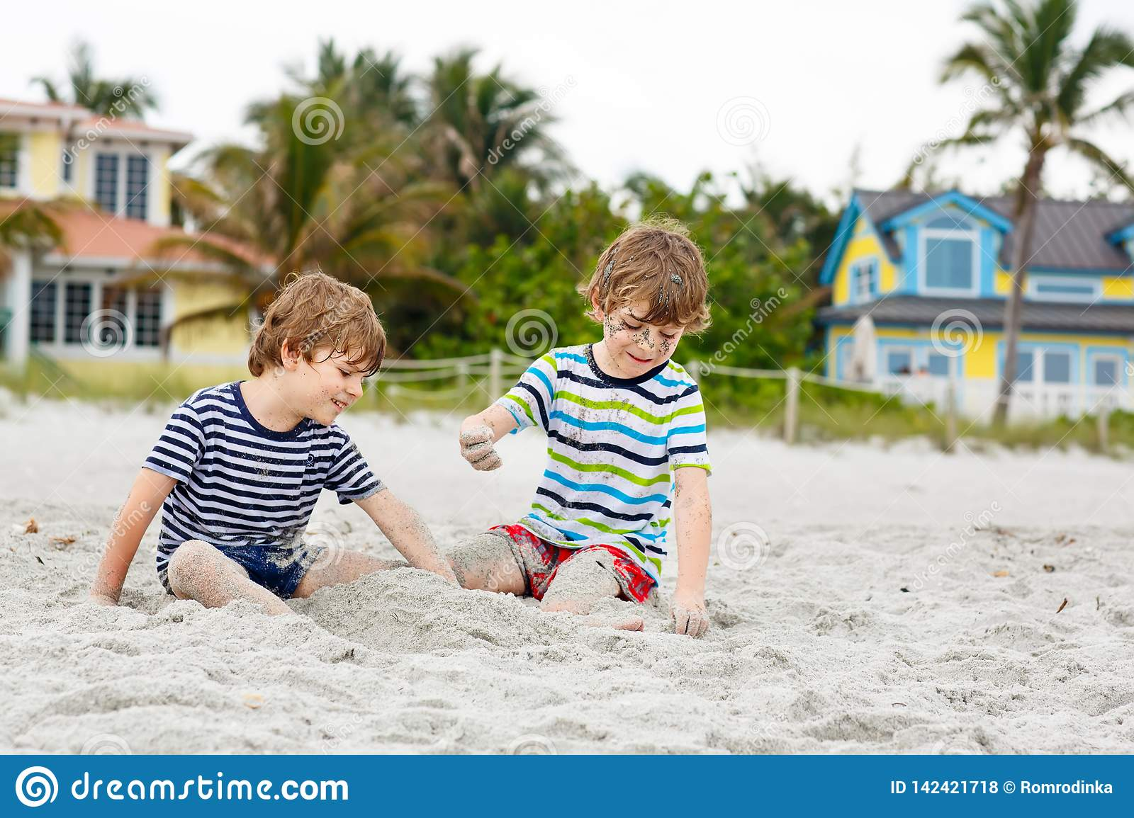 Two little kids boys having fun on tropical beach, happy best friends playing, friendship concept. Siblings brothers