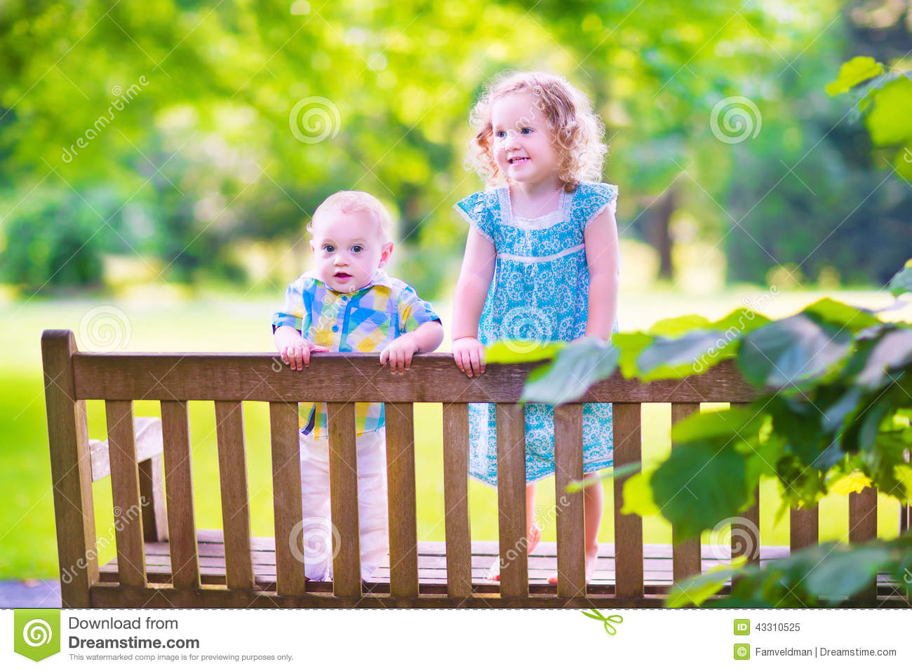 Two little kids on a park bench