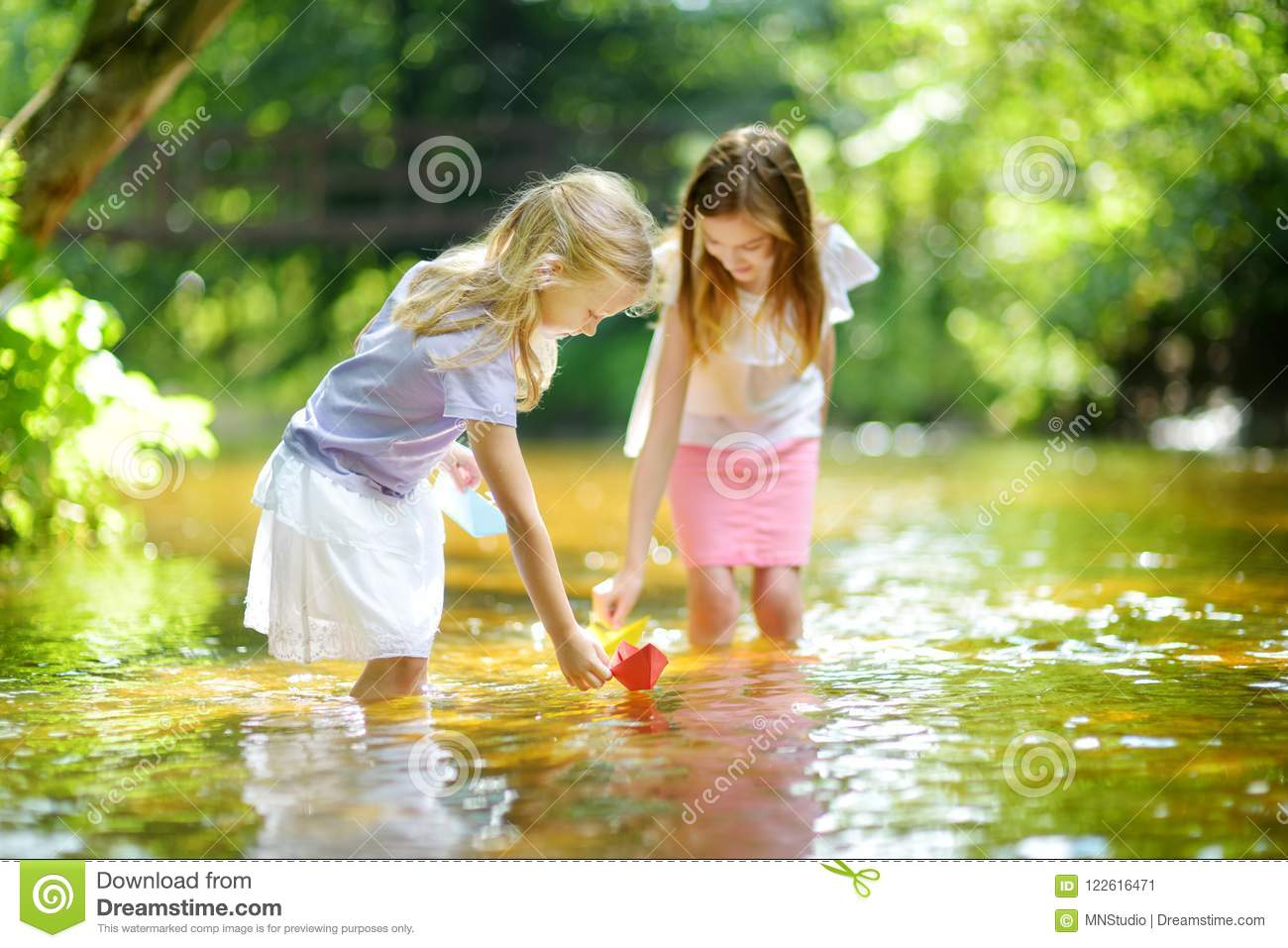 Two little sisters playing with paper boats by a river on warm and sunny summer day. Children having fun by the water.