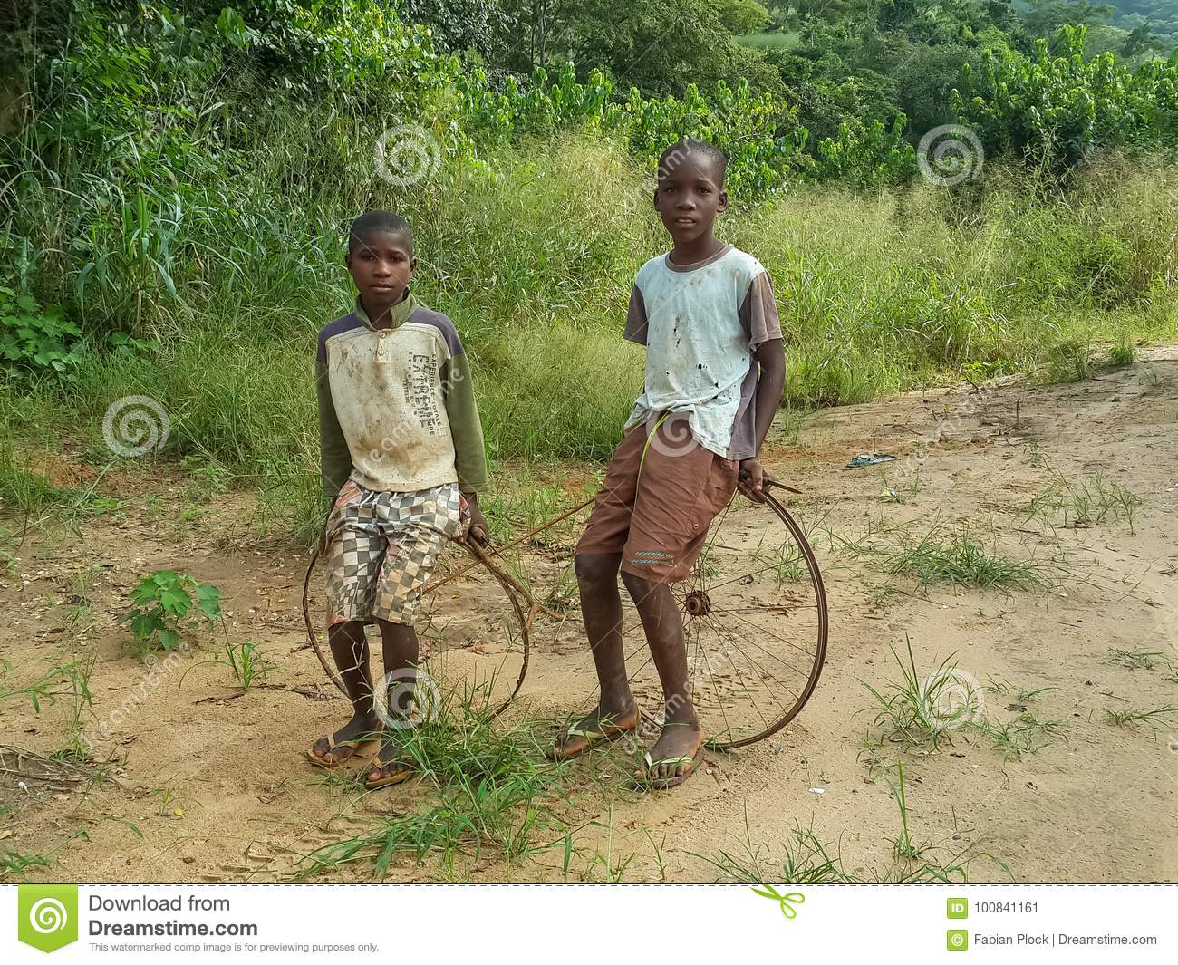 Toys From Africa : Two local african boys sitting on their simple bicycle wheel and