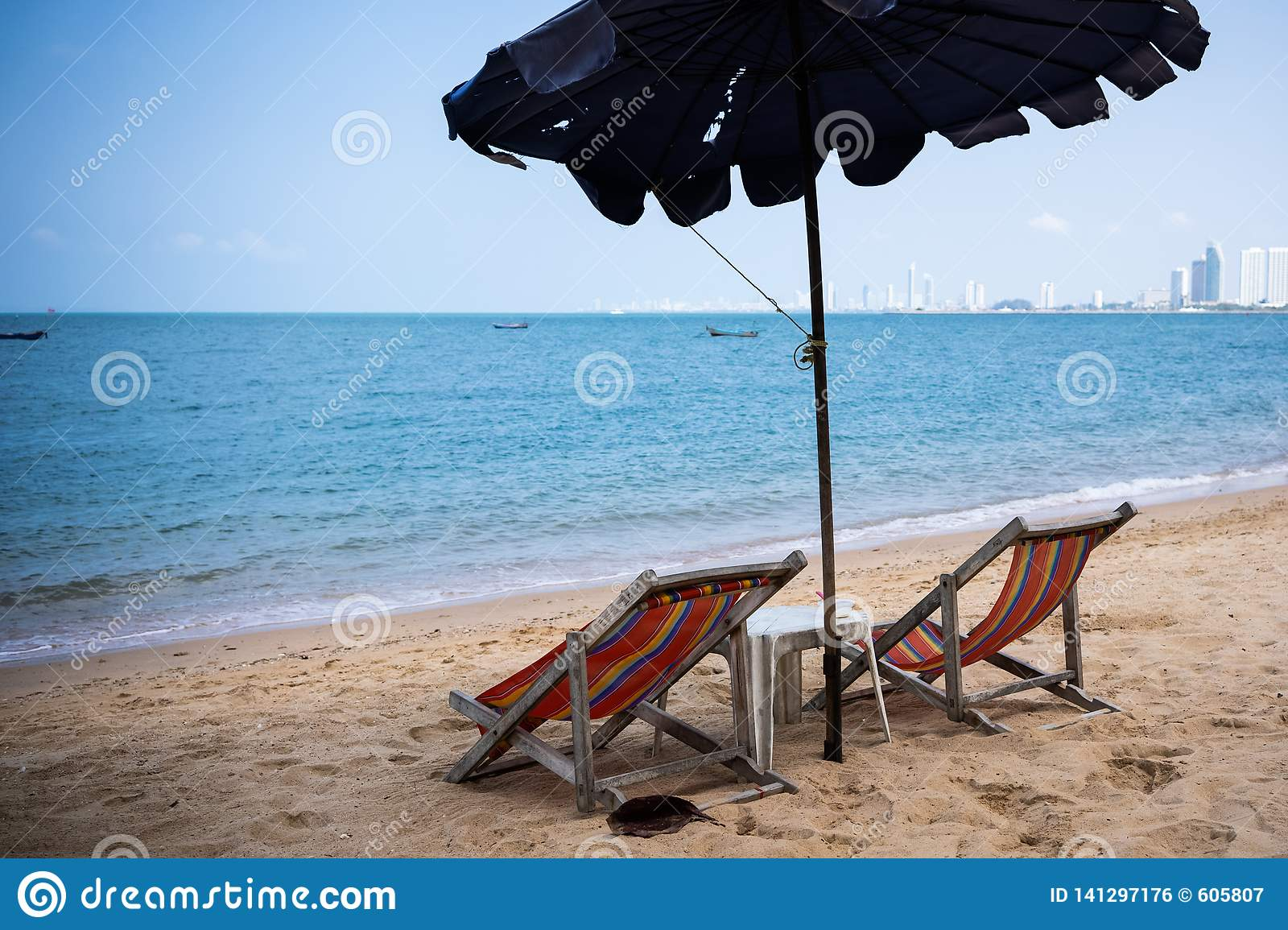 Two loungers and an umbrella on the blue sea on the beach of Pattaya, Thailand. back view.