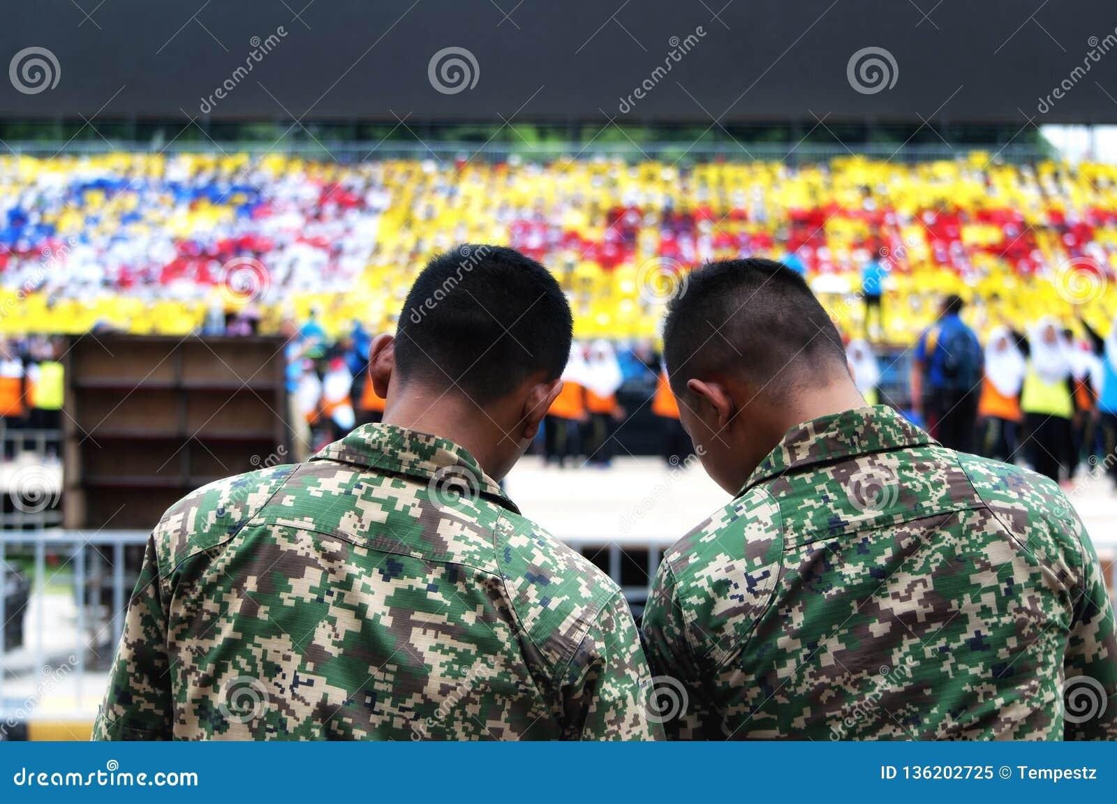 Malaysian army men watching students practicing for Hari Merdeka in Malaysia, Kuala Lumpur