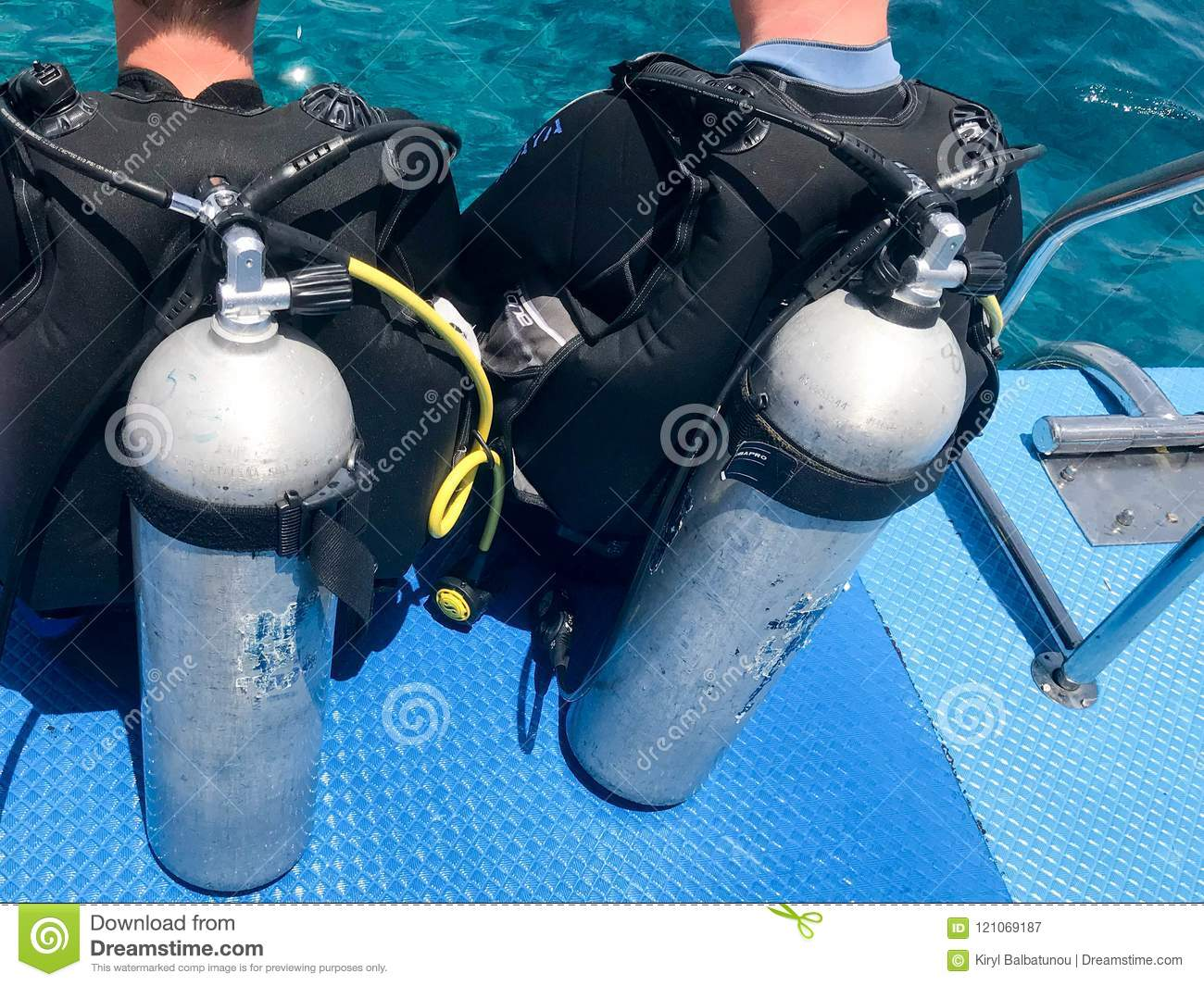 Two male divers in black diving waterproof suits with shiny metal aluminum canisters are preparing to dive from the boat to the bl