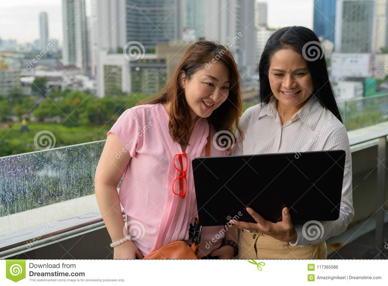 Portrait Of Two Mature Asian Women Together Against View Of The City In Bangkok Thailand