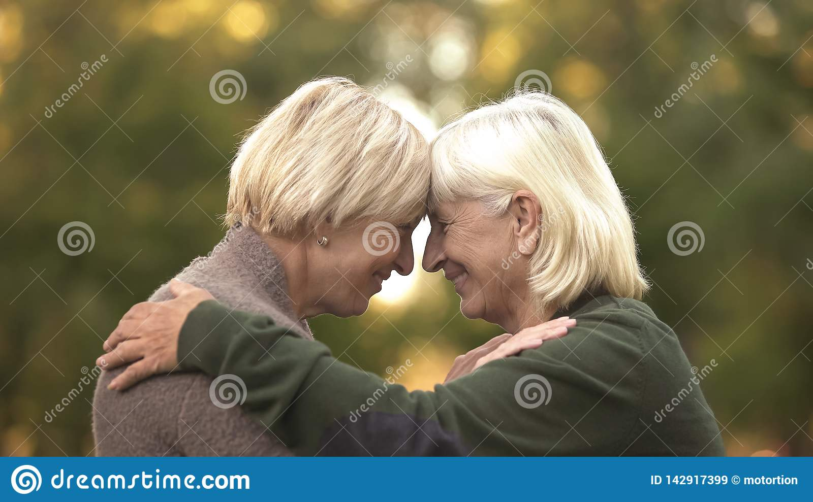 Two mature female friends tightly hugging each other and smiling, happy meeting
