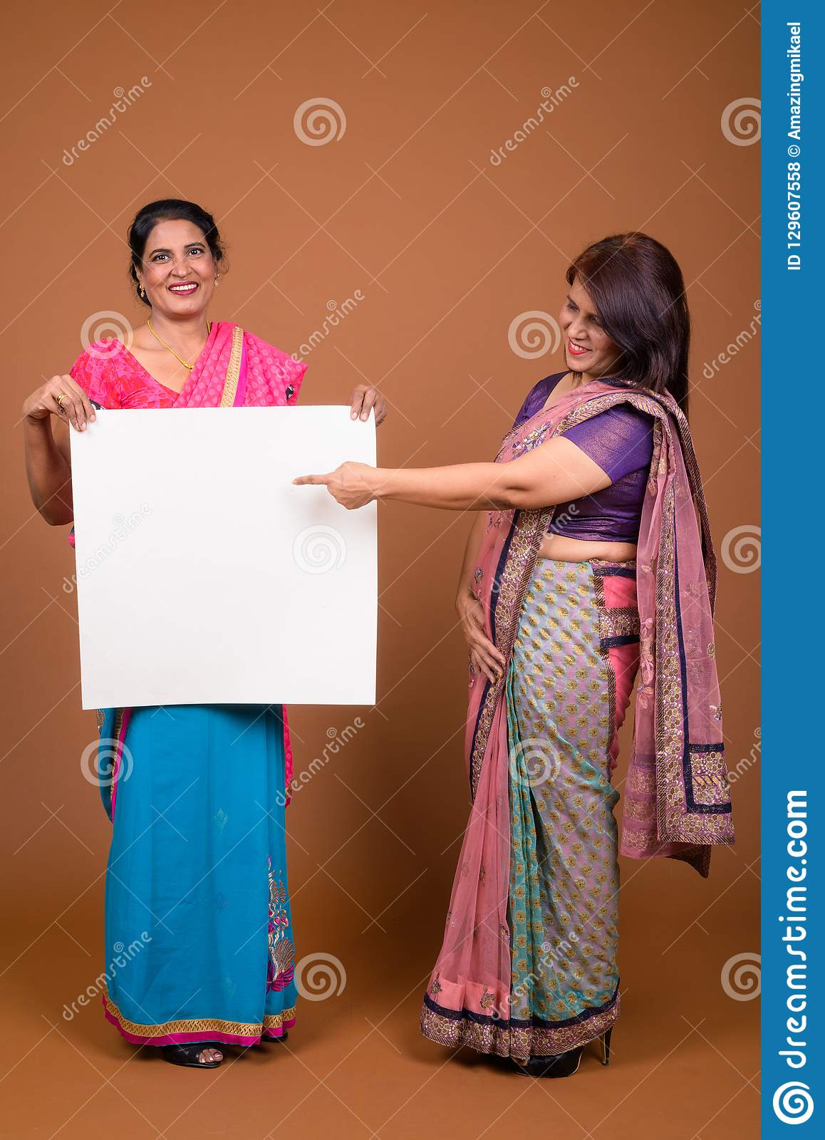 Studio shot of two mature Indian women wearing Sari Indian traditional  clothes together against brown background