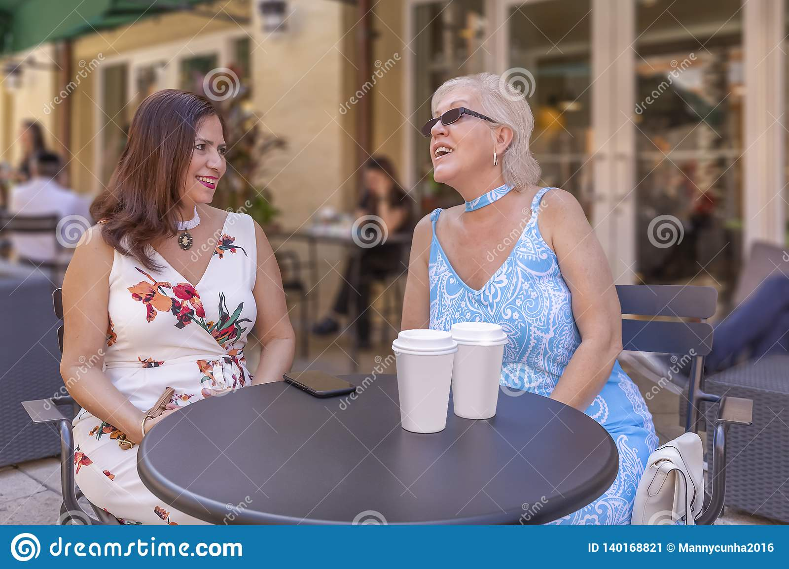 Two mature ladies enjoy a cup of coffee at the outdoor cafe