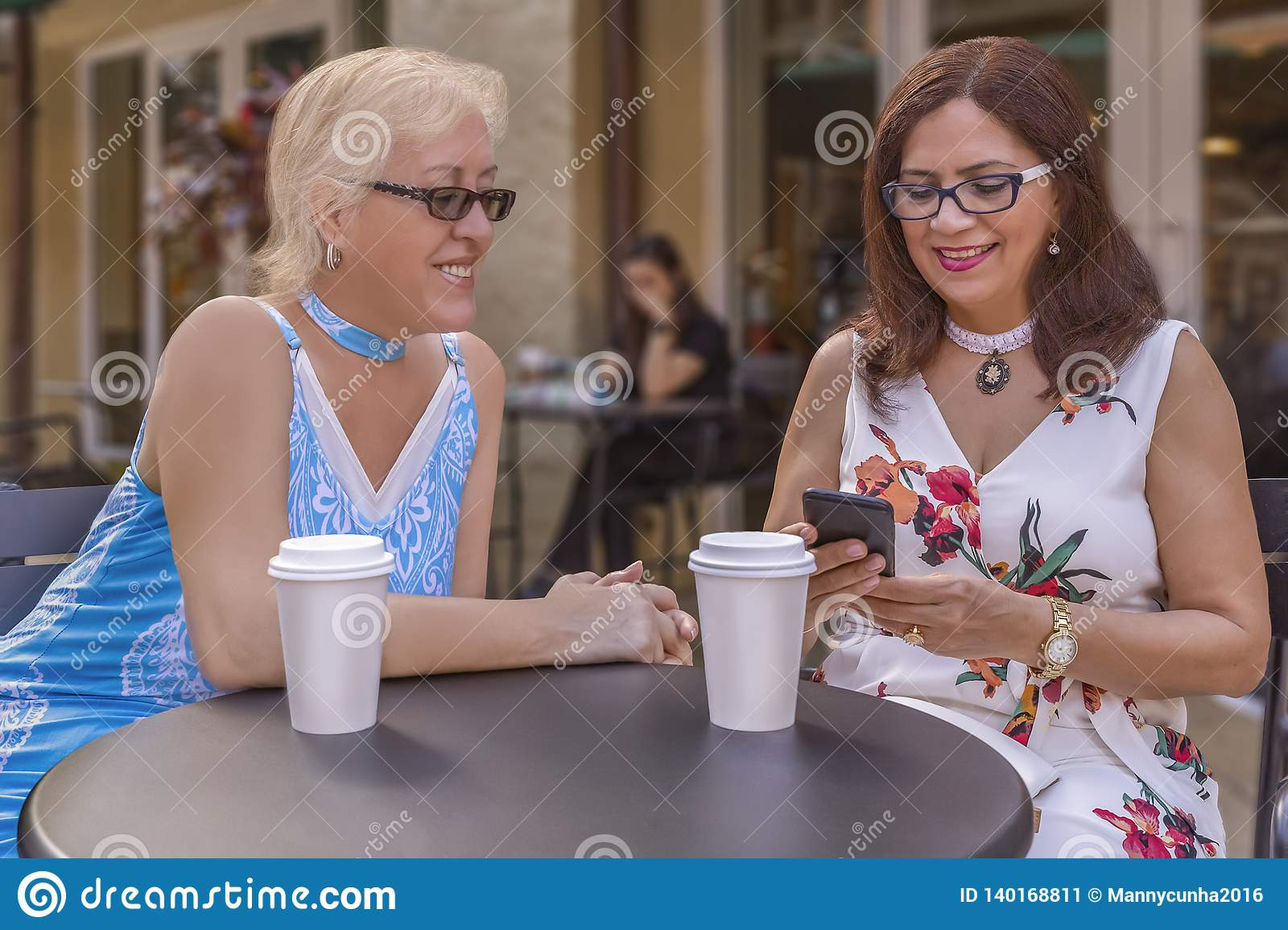 Two mature friends enjoy coffee outdoors while looking at the smartphone