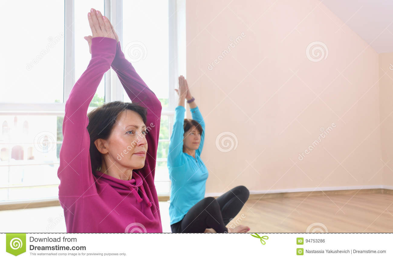 two mature women doing yoga exercise in fitness studio stock photo