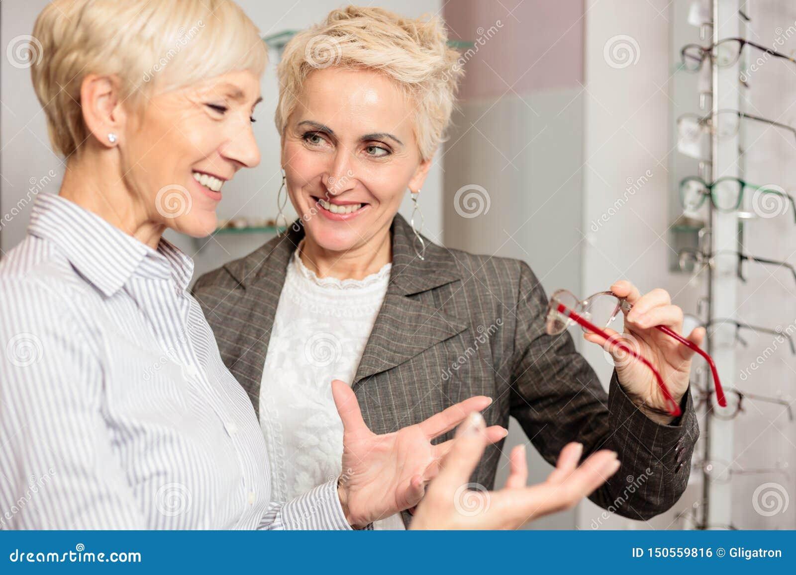 Two mature women shopping and choosing prescription eyeglasses