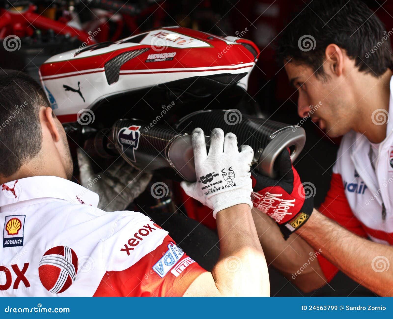 Two mechanics change the exhaust pipe