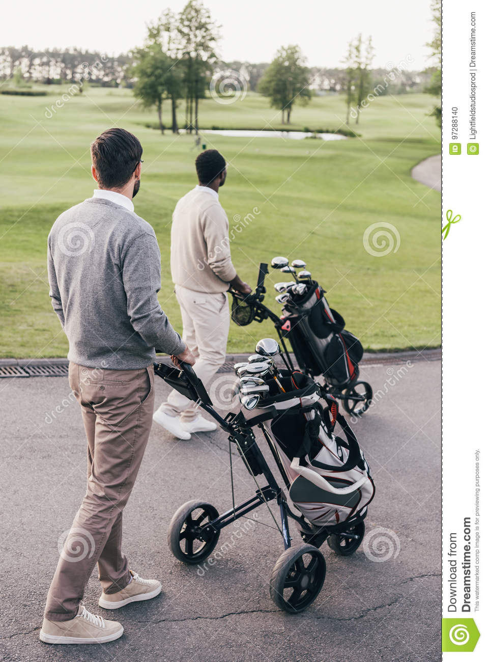 Two men carrying golf clubs in golf bags and walking at golf course