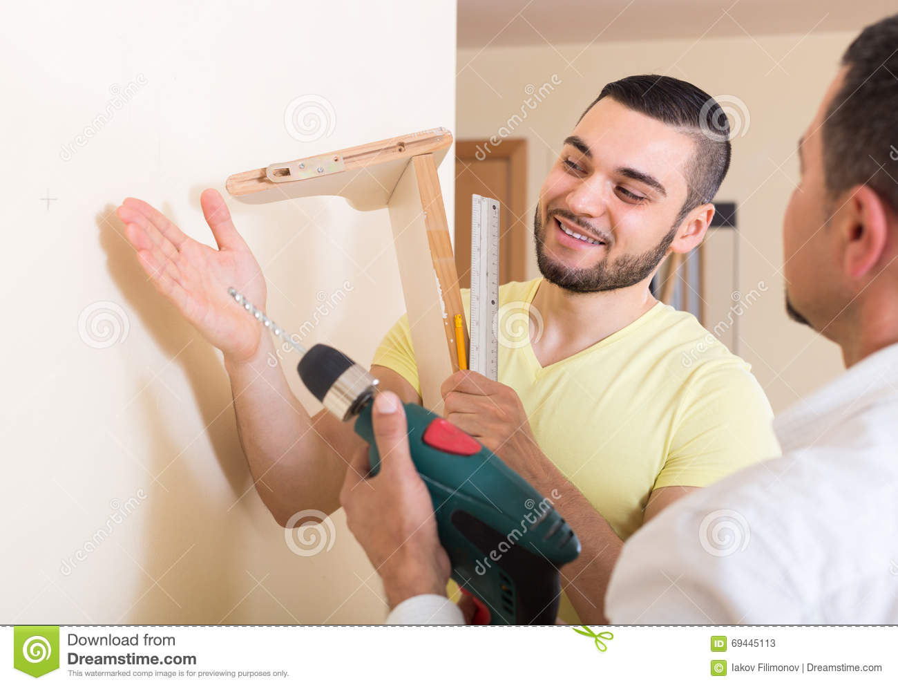 Two men with drill and level