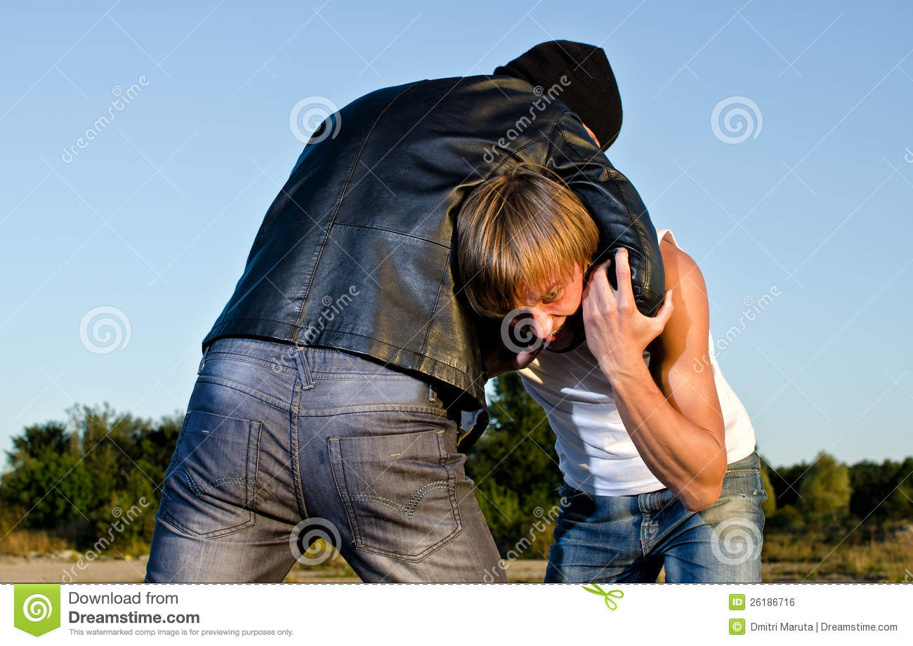 Two men fight outdoors.