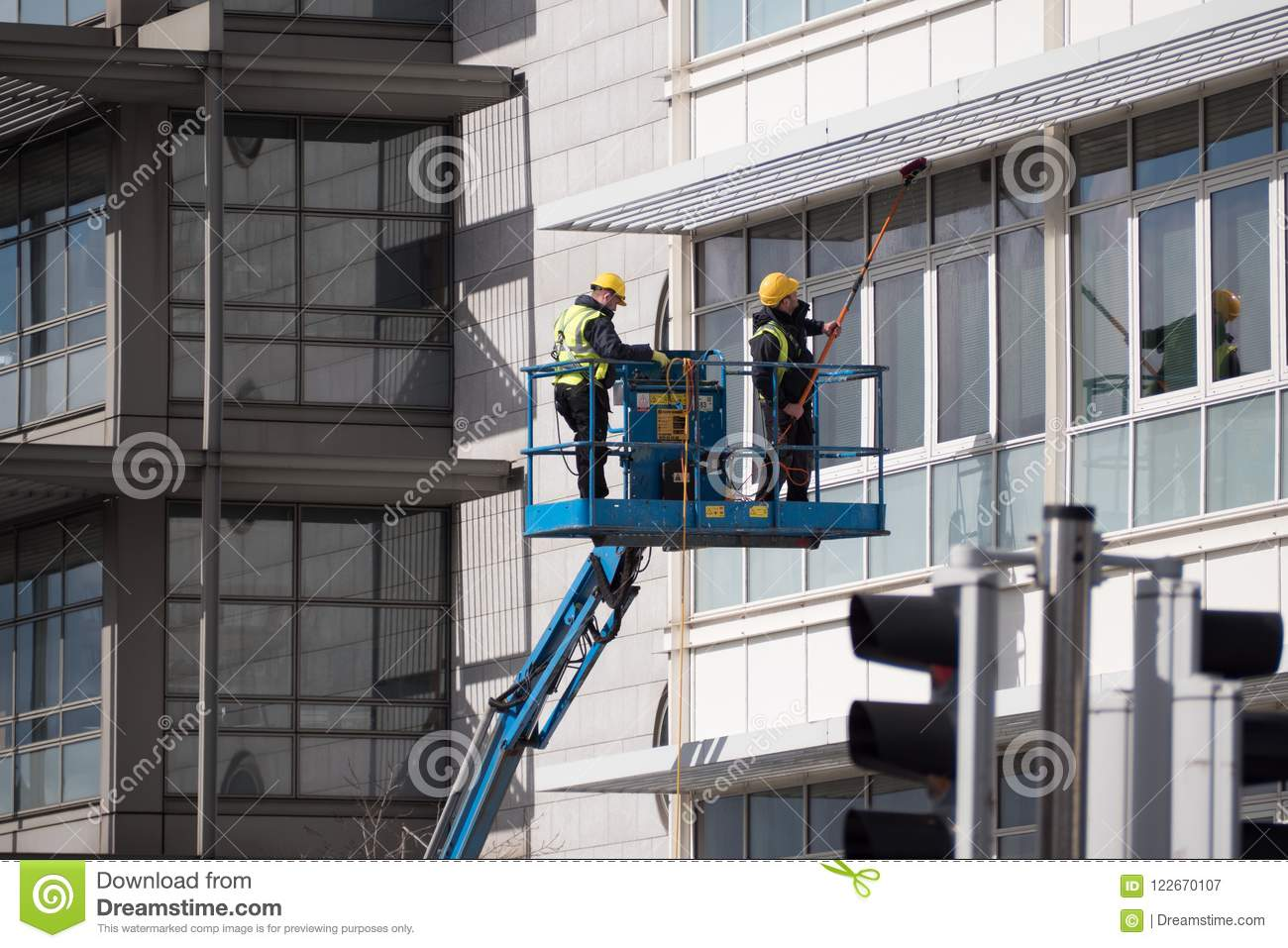 Two Men In Hard Hats Cleaning Tall Building Windows Using Hydraulic