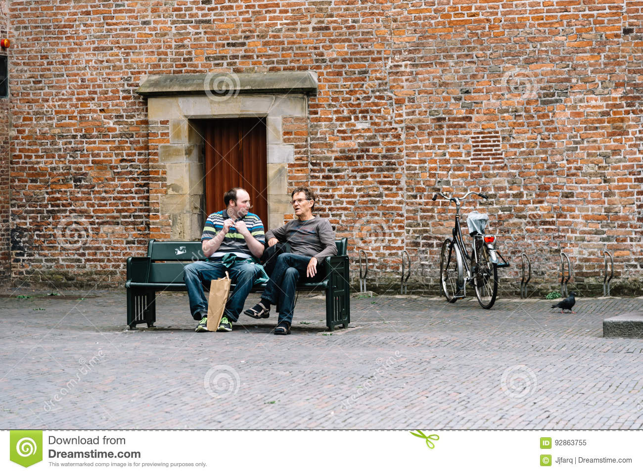 Two Men Sitting On A Publick Bench In Historic Centre Of Utrecht