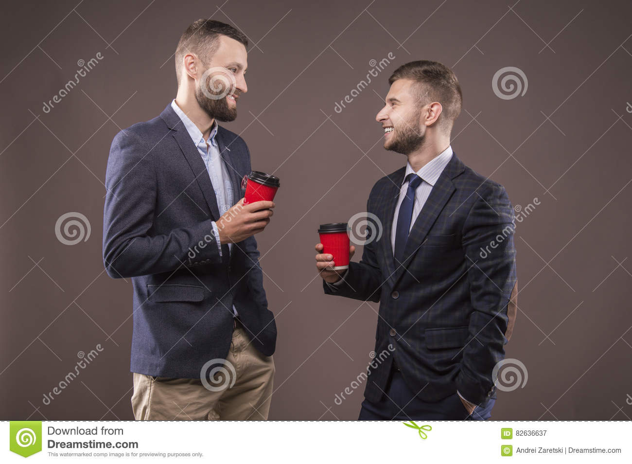 Two men standing with a cup of coffee