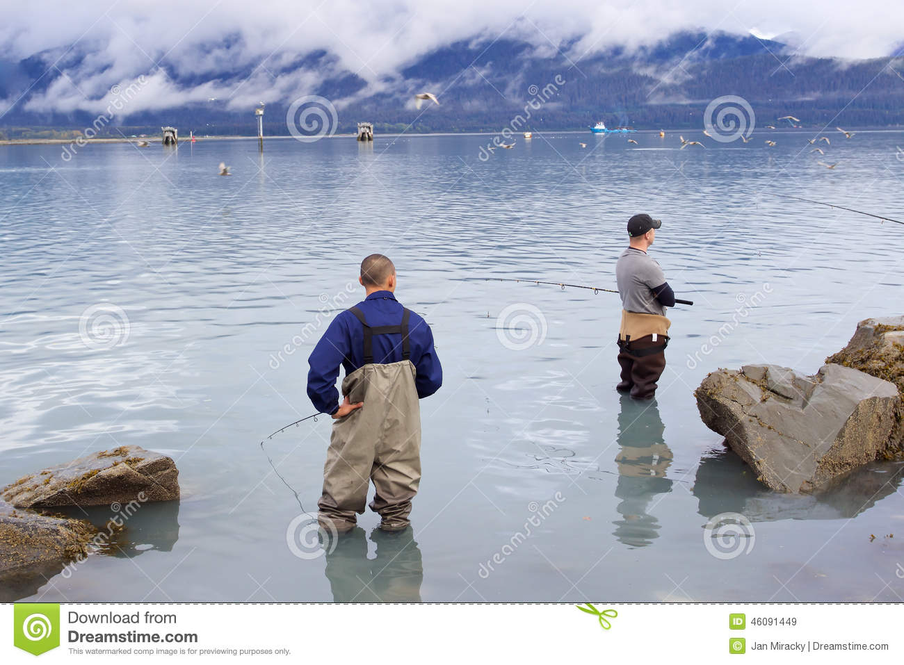 Two men staning in ocean and fishing in seward editorial for Best time to fish in alaska