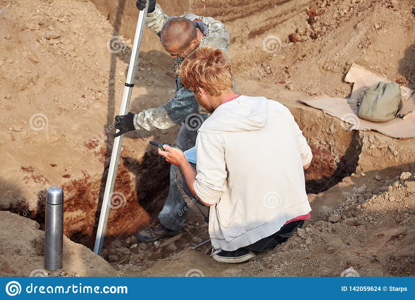 Two men at work outdoors, in digger process. Archaeological excavations.