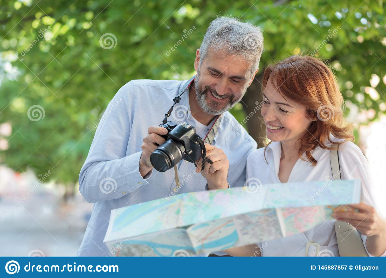 Two mid adult tourists walking through the park, woman is holding a map and man is showing pictures on a digital camera