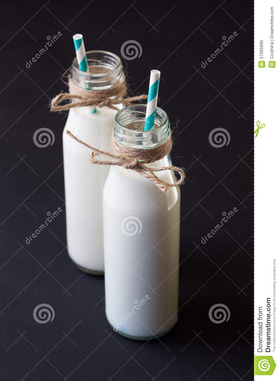 Two milk bottle with blue retro straw on black